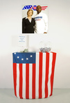 Arlene Rush • Current Affairs Digital print mounted on foam core, printed metal campaign buttons, plexi donation box and digital print sign, glass bowl, Betsy Ross polyester flag and wood shelf
